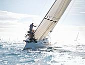 Sailboat heeling on sunny ocean