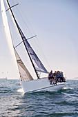 Friends sailing on heeling sailboat