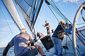 Men sailing adjusting rigging and sail