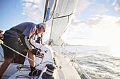 Man sailing pulling rigging on sailboat