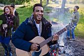 Smiling man playing guitar at campsite
