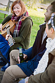 Woman playing guitar with friends