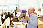 Businessman shouting into megaphone in office