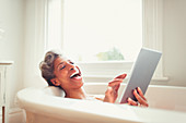 Mature woman using digital tablet in bathtub