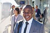 Smiling businessman on train station platform