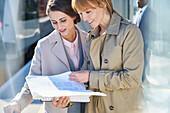 Businesswomen reading paperwork