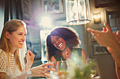 Laughing women friends clapping and dining