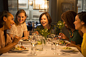 Smiling women friends dining at restaurant table