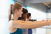 Women stretching arms in exercise class gym studio
