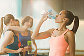 Woman drinking water in exercise class gym studio