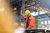 Steel worker fastening chain in factory