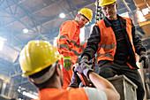 Steel workers fastening crane hook to steel