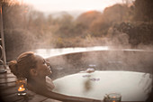 Serene woman soaking in steaming hot tub