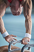 Male gymnast upside-down on pommel horse
