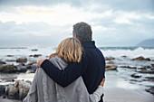 Serene couple hugging on winter beach