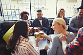Laughing friends toasting beer glasses in bar