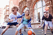 Friends playing basketball on basketball court