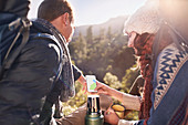 Young couple hiking, taking a coffee