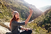 Young woman taking selfie with camera phone