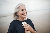 Senior woman holding cell phone on beach