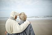 Pensive senior couple hugging on beach