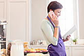 Female caterer baking and using tablet