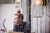 Young woman at laptop looking out cafe window