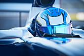Formula one race car driver wearing blue helmet