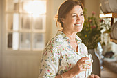 Smiling mature woman drinking wine in kitchen