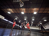 Young basketball players playing basketball in gym