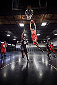 Young basketball player jumping to slam dunk