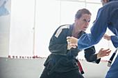 Determined, tough woman practicing jiu-jitsu in gym