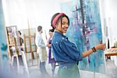 Portrait female artist lifting painting