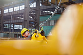 Male factory worker attaching chain to equipment