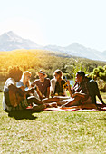 Young friends enjoying picnic in grass