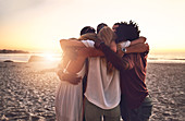 Young friends hugging in a huddle on sunset beach