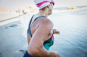 Female swimmer running into ocean