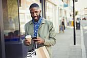 Young man texting on urban sidewalk
