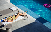 Woman sunbathing on lounge chair at sunny poolside