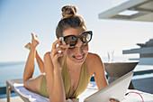 Smiling woman using digital tablet, sunbathing