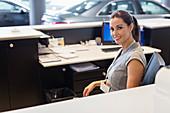 Portrait receptionist working at desk in showroom