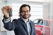 Portrait car salesman holding, showing car key