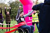 Man in wheelchair crossing race finish line