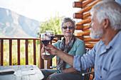 Active senior couple toasting red wine glasses