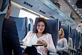 Portrait businesswoman using smart phone on train