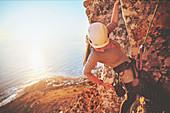 Female rock climber reaching for clip
