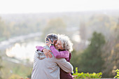 Affectionate active senior couple hugging in nature