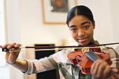 Portrait confident teenage girl playing violin