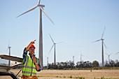 Engineer with walkie-talkie at wind turbine power plant