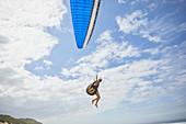 Female paraglider paragliding against blue sky
